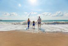 עצמאות כלכלית - זוג עומד על חוף הים מביט לעבר האופק עם ילדם הקטן לאחר פרישה מוקדמת וחופש כלכלי
