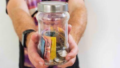 איש עם שעון מושיט ידיים ומחזיק צנצנת מלאה בכסף - ההבדל בין קרנות צוברות וקרנות מחלקות